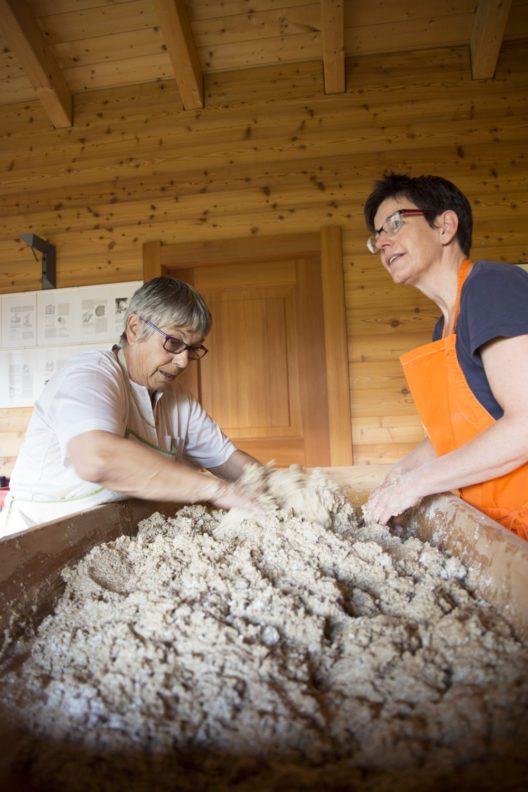 Weiter geht es mit der Verarbeitung im Backhaus. Dort kneten freiwillige Bäckerinnen das Brot...