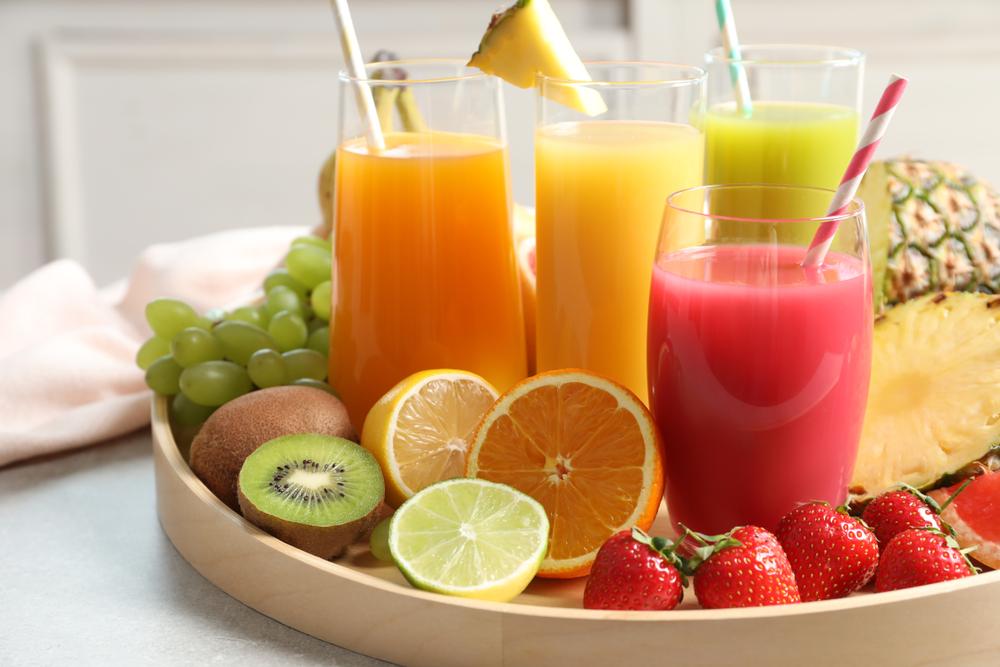 Obst liegt auf einem Serviertablett neben vier Gläsern voller unterschiedlicher Fruchtsäfte.