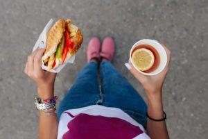 Eine Frau hält einen Becher mit Tee und einen Burger in den Händen