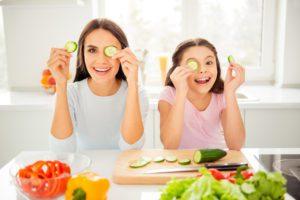 Mutter und Tochter halten sich eine Gurkenscheibe ans Auge