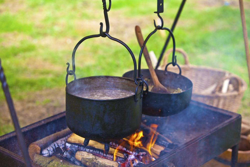 Metalltöpfe hängen über einem offenen Feuer und kochen