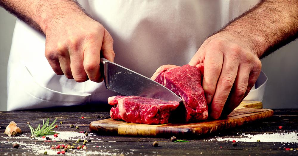 Koch schneidet Fleisch in Stücke