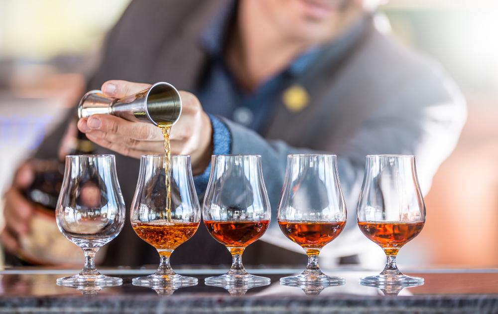 Bartender Profi, der fünf alkoholische Getränke zubereitet.